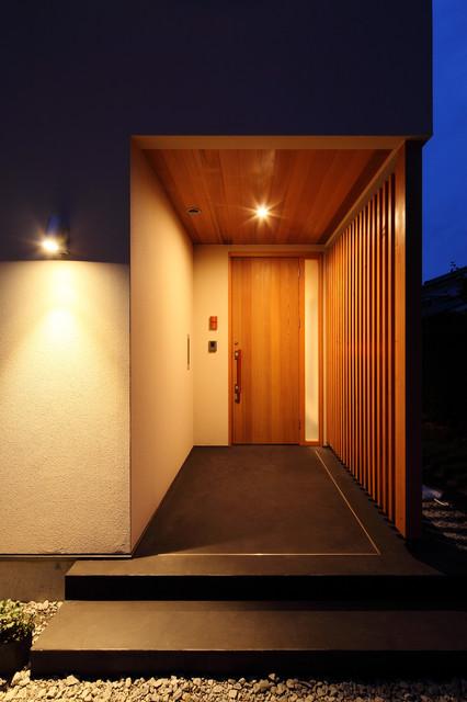 他の地域, の片開きドア和風の玄関の写真 (ベージュの壁、コンクリートの床、茶色いドア、黒い床)