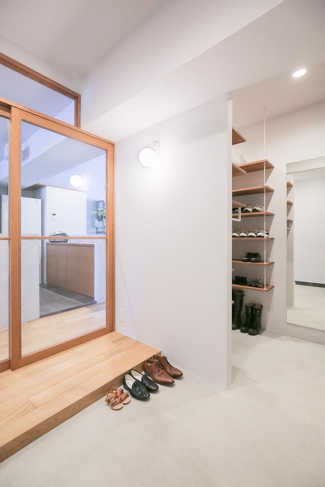 Esempio di un ingresso o corridoio minimalista con pareti bianche, pavimento in cemento e pavimento grigio
