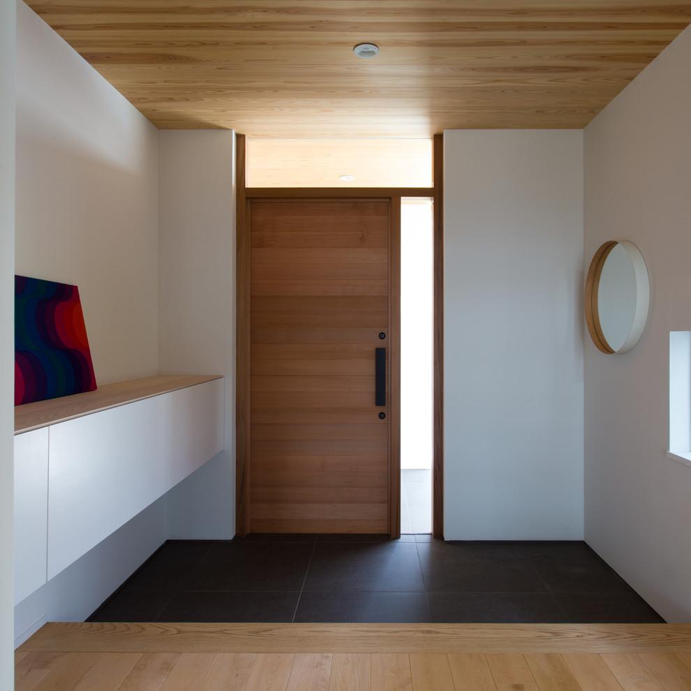名古屋の片開きドアモダンスタイルの玄関ホールの画像 (白い壁、木目調のドア、黒い床)