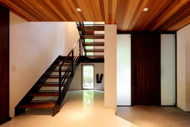 他の地域, の中サイズの片開きドアモダンスタイルの玄関ホールの写真 (白い壁、磁器タイルの床、茶色いドア、白い床)