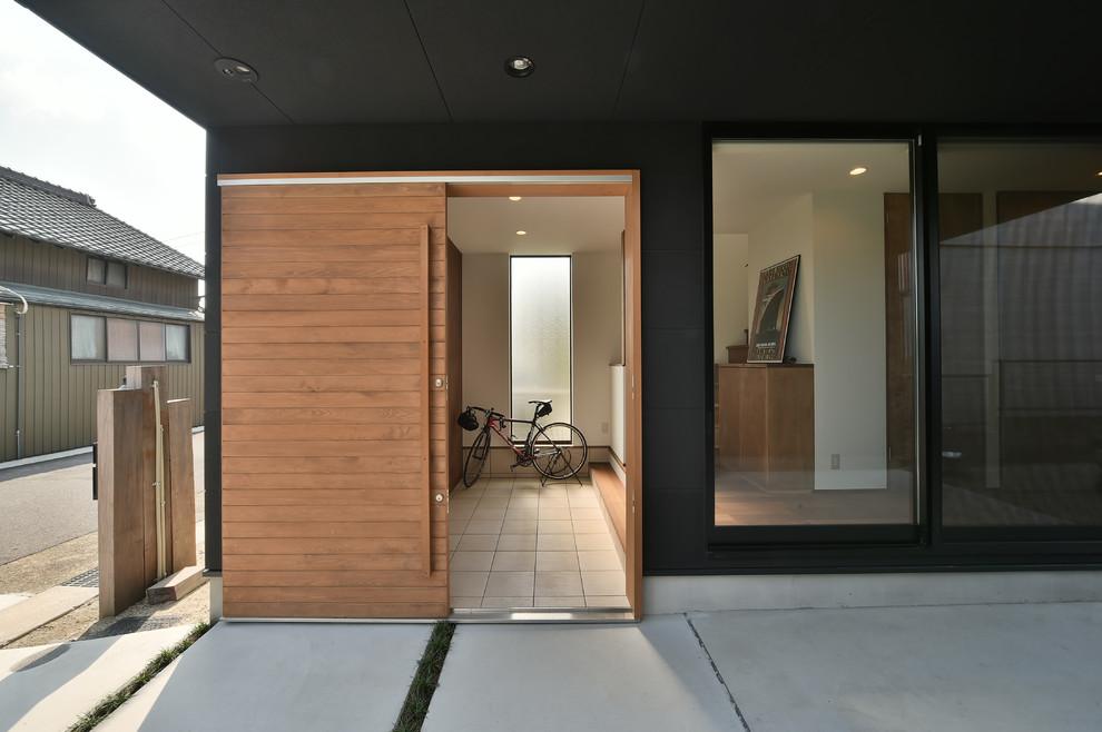 名古屋の引き戸アジアンスタイルの玄関の画像 (黒い壁、淡色木目調のドア、グレーの床)