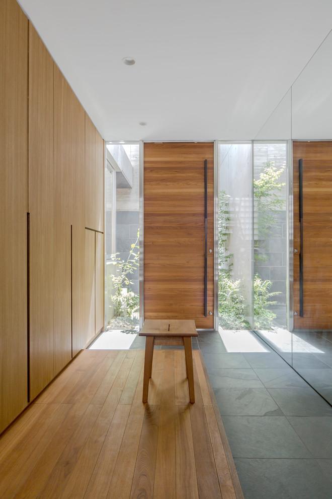 Immagine di un ingresso o corridoio moderno con pareti marroni, una porta singola, una porta in legno bruno e pavimento marrone