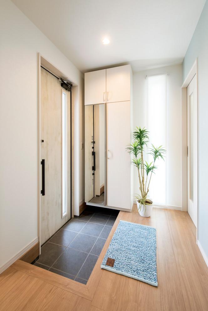 福岡の小さい片開きドアビーチスタイルの玄関の画像 (白い壁、淡色木目調のドア、黒い床)