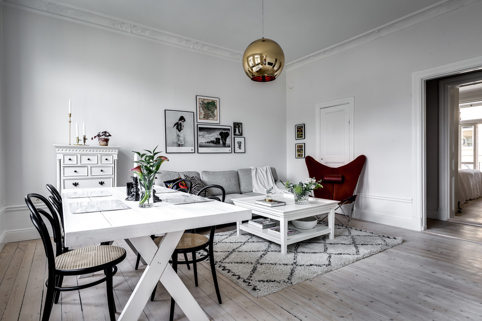 Family room - scandinavian open concept light wood floor and gray floor family room idea in Stockholm with white walls