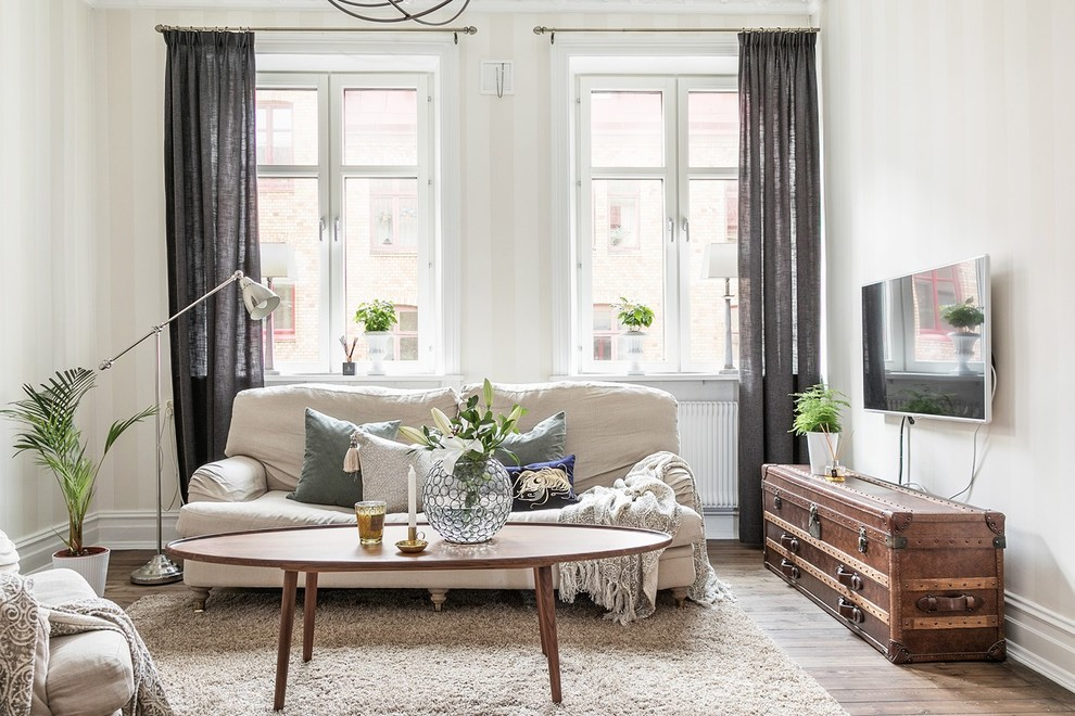 Inspiration for a scandinavian medium tone wood floor and brown floor family room remodel in Gothenburg with white walls and a wall-mounted tv