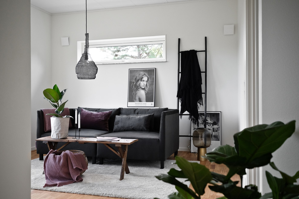 Example of a danish enclosed medium tone wood floor family room design in Stockholm with white walls