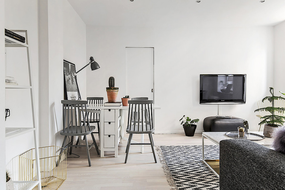 Inspiration for a small scandinavian enclosed light wood floor family room remodel in Stockholm with white walls and a wall-mounted tv