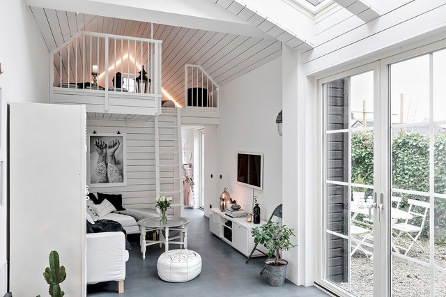 Small danish open concept gray floor and concrete floor family room photo in Malmo with white walls and a wall-mounted tv