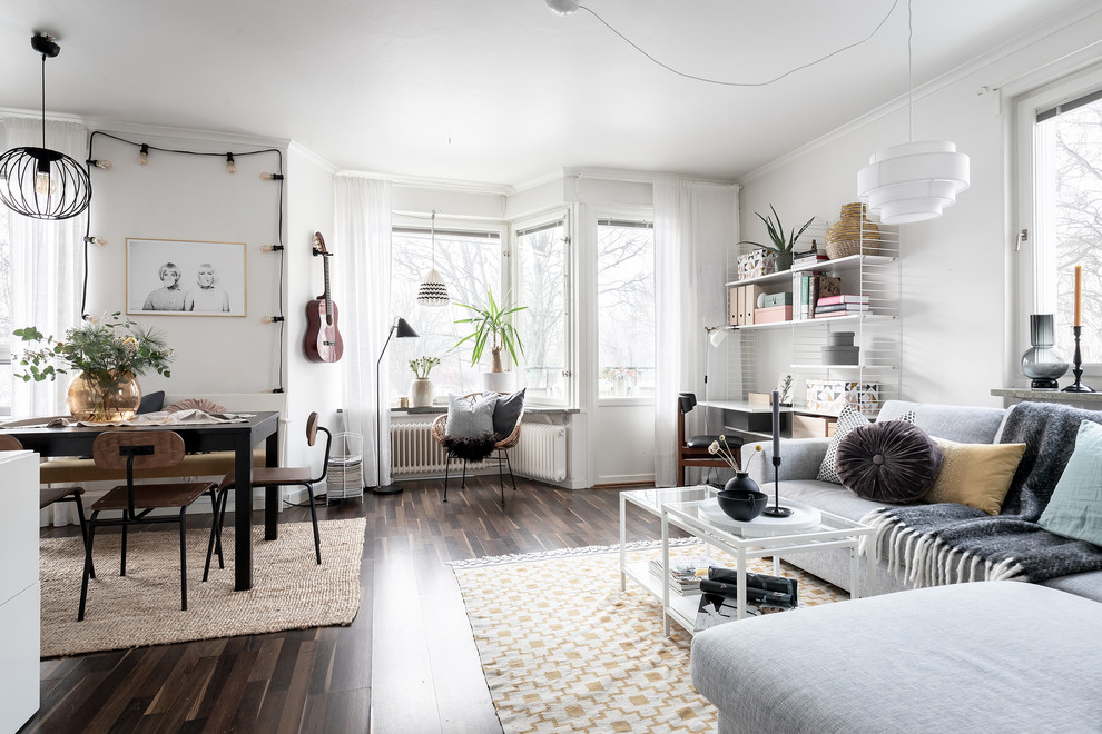 Example of a danish open concept dark wood floor and brown floor family room design in Stockholm with white walls