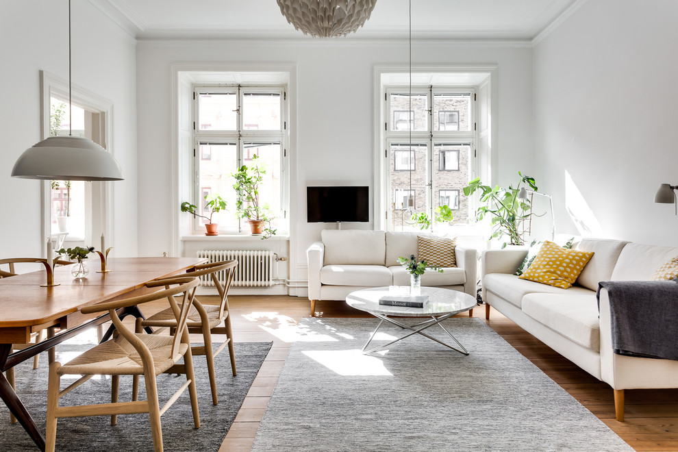 Danish open concept medium tone wood floor and brown floor family room photo in Stockholm with white walls and a wall-mounted tv