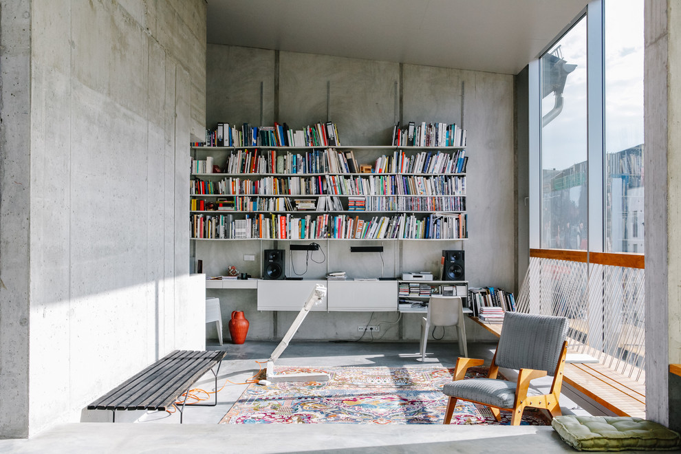 Inspiration for a mid-sized industrial built-in desk concrete floor home office remodel in Berlin with gray walls and no fireplace