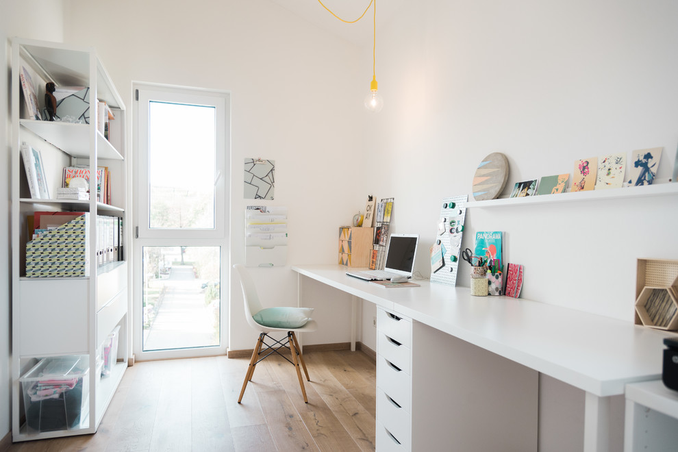 Mid-sized danish freestanding desk light wood floor and beige floor study room photo in Other with white walls and no fireplace