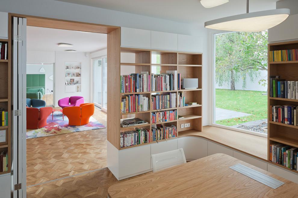 Mittelgroßes Modernes Lesezimmer ohne Kamin mit weißer Wandfarbe, braunem Holzboden, freistehendem Schreibtisch und braunem Boden in Berlin
