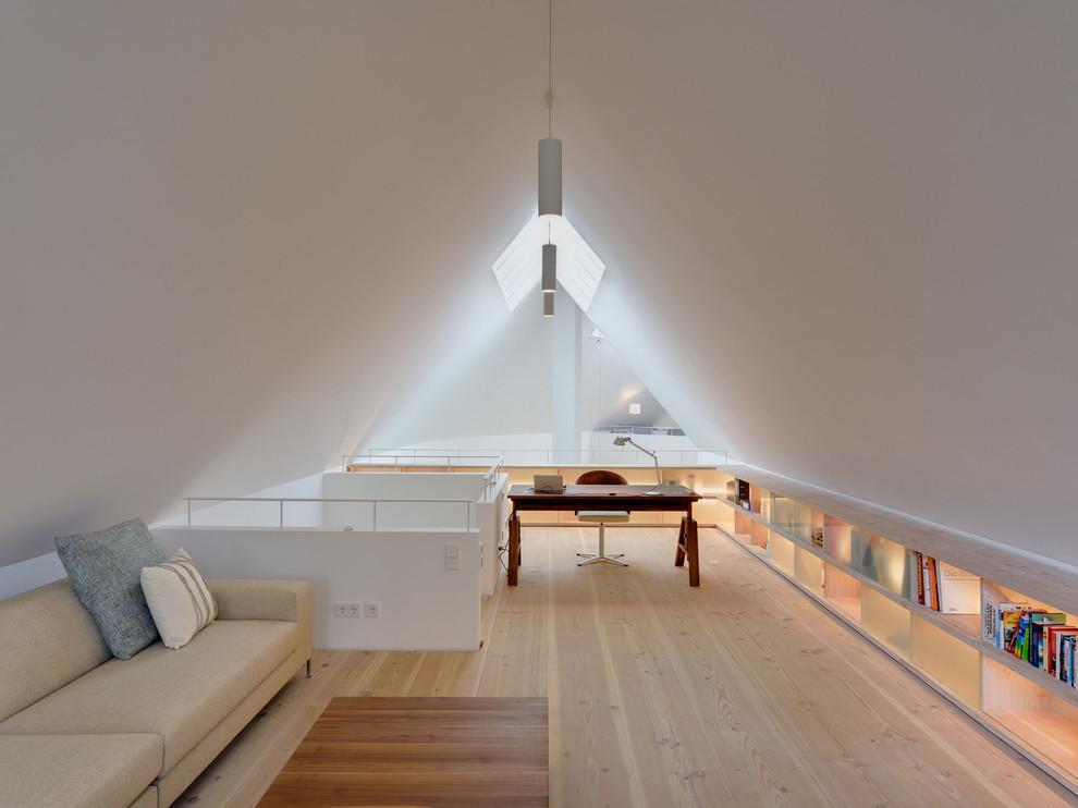 Cette photo montre un grand bureau tendance avec un mur blanc, un sol en bois clair, aucune cheminée et un bureau indépendant.