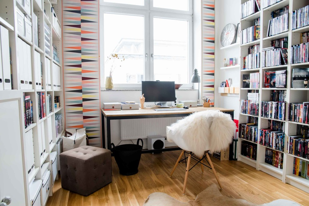 Example of a small danish freestanding desk medium tone wood floor study room design in Berlin with multicolored walls and no fireplace