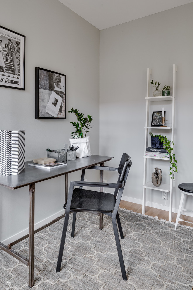 Inspiration for a mid-sized scandinavian freestanding desk light wood floor study room remodel in Gothenburg with gray walls