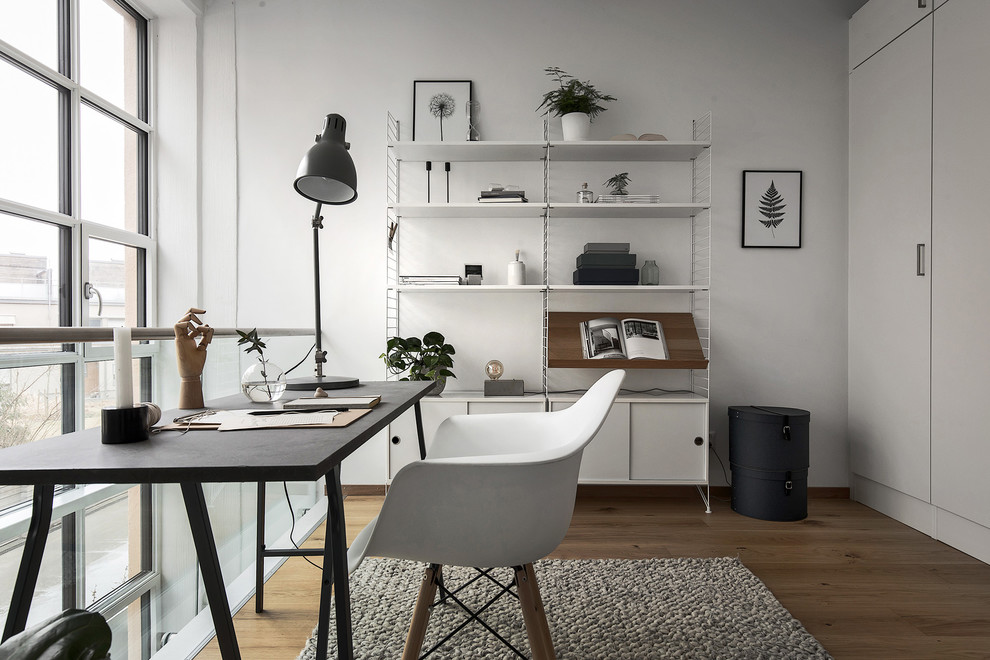 Inspiration for a mid-sized scandinavian freestanding desk medium tone wood floor home office remodel in Stockholm with white walls