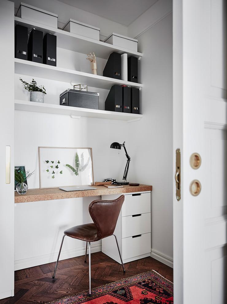 Danish built-in desk dark wood floor and brown floor home office photo in Gothenburg with white walls