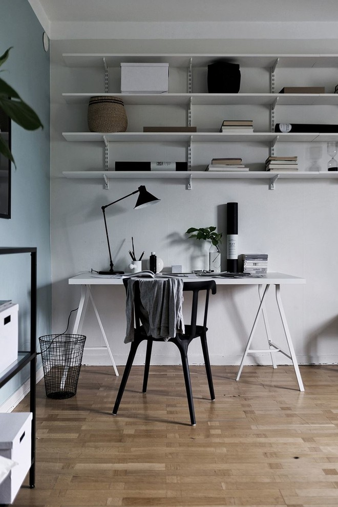 Home office - mid-sized scandinavian freestanding desk medium tone wood floor and brown floor home office idea in Stockholm with multicolored walls