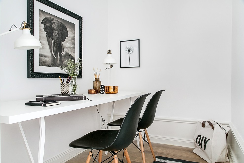 Study room - mid-sized scandinavian freestanding desk light wood floor study room idea in Stockholm with white walls and no fireplace