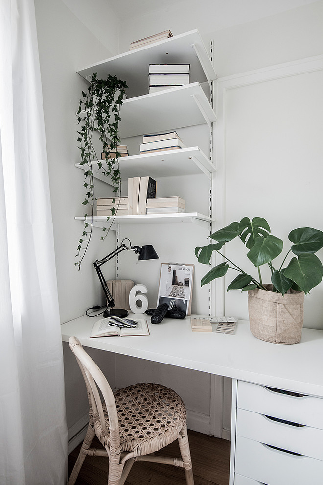 Inspiration for a scandinavian built-in desk dark wood floor and brown floor home office remodel in Stockholm with white walls