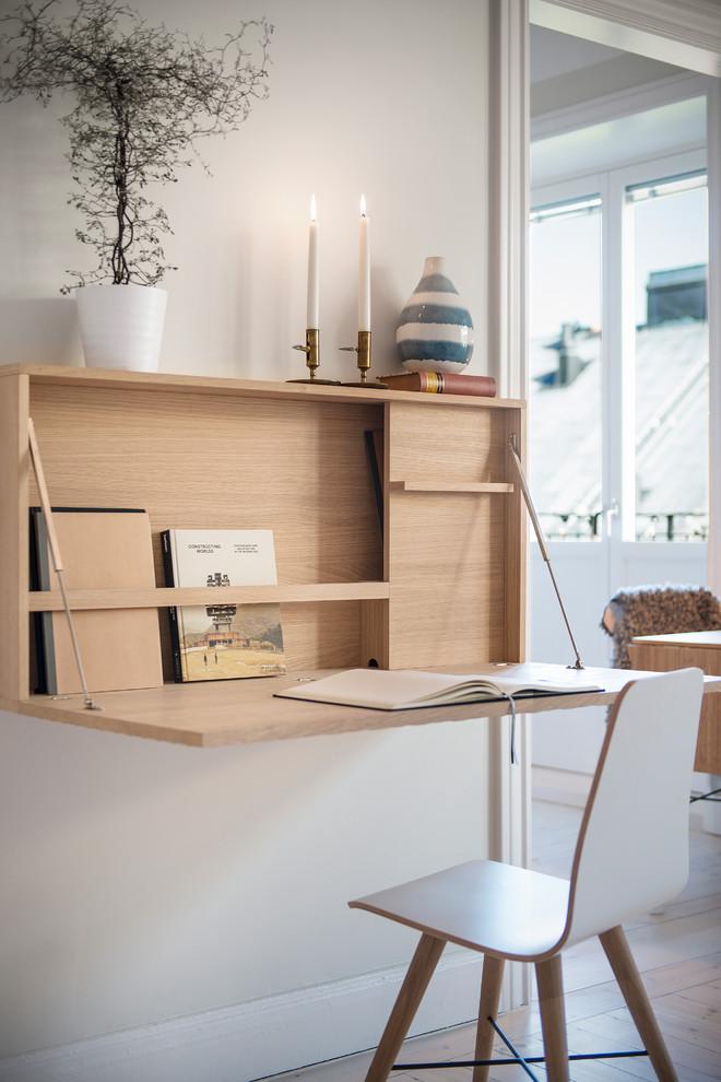 Réalisation d'un grand bureau nordique avec un mur gris, un sol en bois brun, aucune cheminée et un bureau intégré.