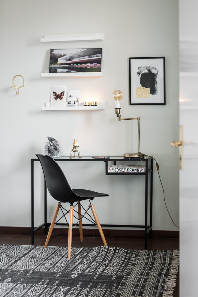 Example of a mid-sized danish freestanding desk dark wood floor study room design in Stockholm with white walls