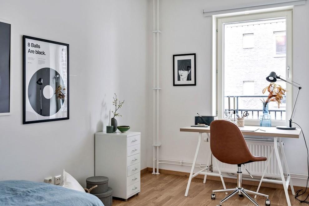 Minimalistisk inredning av ett arbetsrum, med vita väggar, mellanmörkt trägolv, ett fristående skrivbord och brunt golv