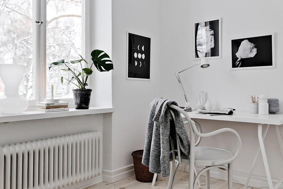 Mid-sized danish freestanding desk light wood floor study room photo in Stockholm with white walls
