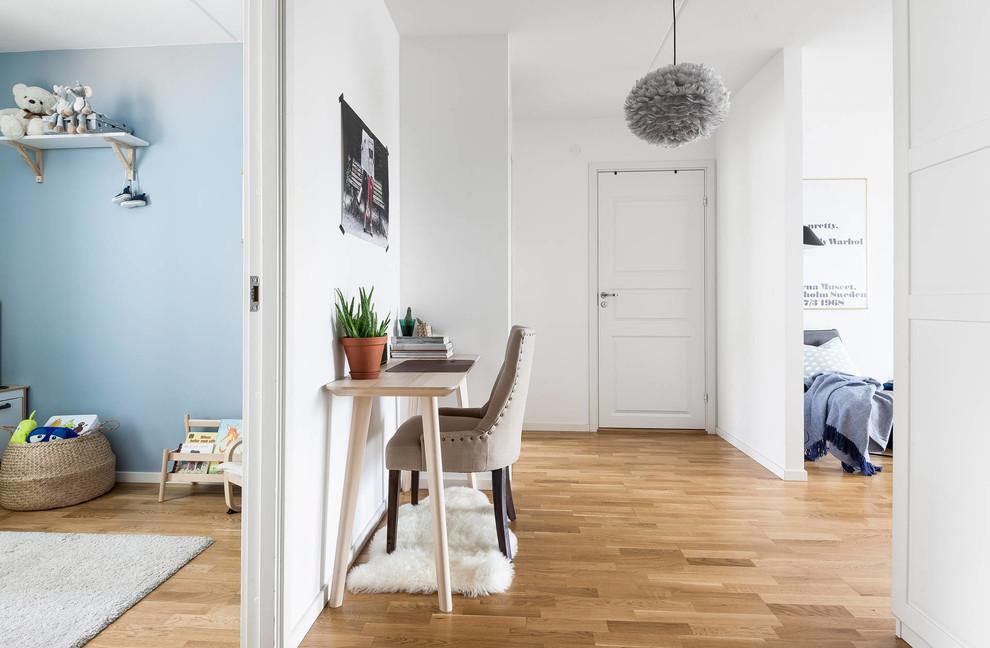 Foto på ett skandinaviskt arbetsrum, med mellanmörkt trägolv, ett fristående skrivbord och brunt golv