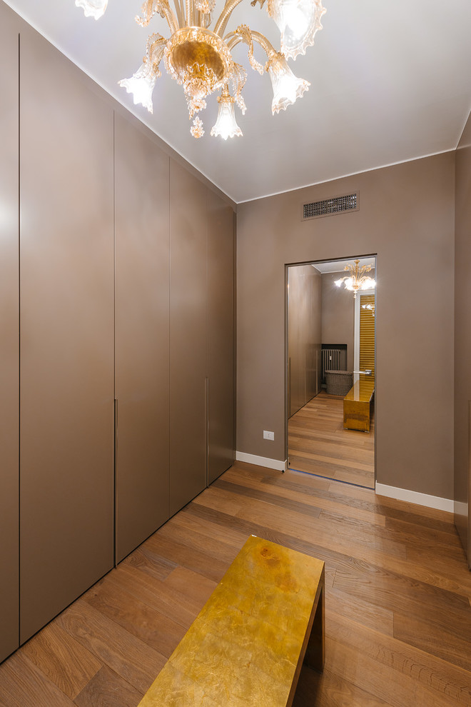 Inspiration for a large contemporary gender-neutral medium tone wood floor dressing room remodel in Milan with flat-panel cabinets and brown cabinets