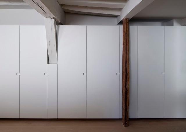 Foto de armario unisex, contemporáneo, grande, con armarios con paneles lisos, puertas de armario blancas y suelo de madera en tonos medios
