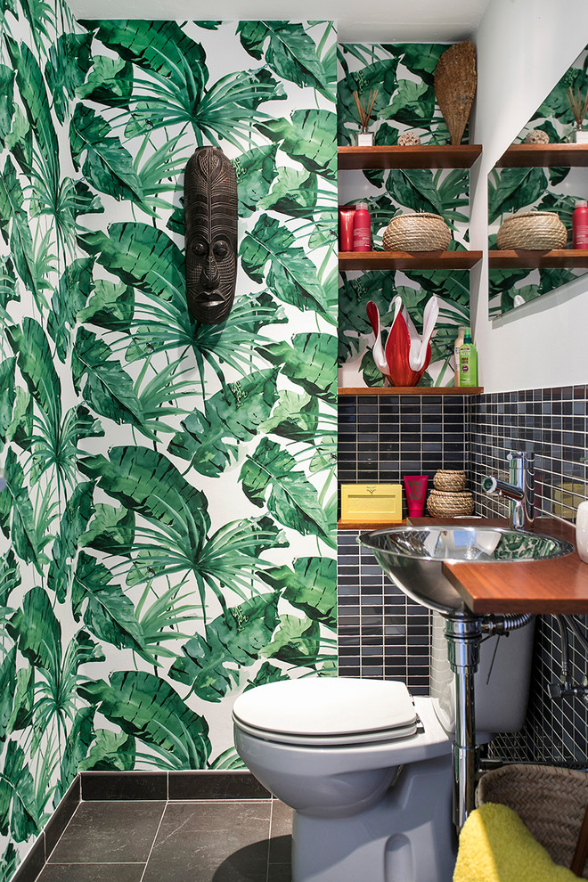 Powder room - small tropical black tile gray floor powder room idea in Barcelona with a two-piece toilet, multicolored walls and a drop-in sink