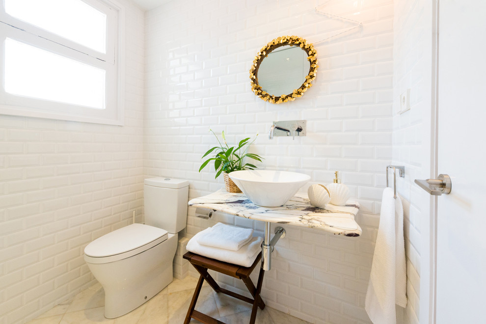Small danish subway tile and white tile travertine floor powder room photo in Barcelona with a two-piece toilet, white walls, a vessel sink and marble countertops