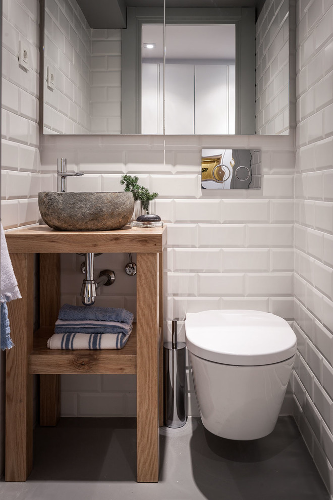 Powder room - small scandinavian white tile gray floor powder room idea in Bilbao with open cabinets, medium tone wood cabinets, a wall-mount toilet, white walls and a vessel sink