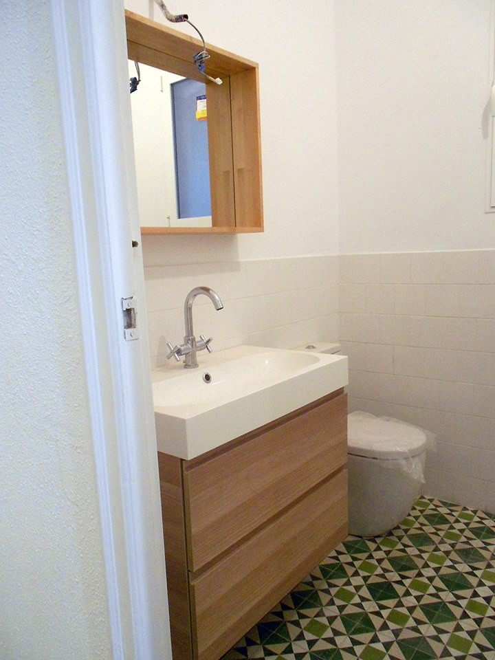 Small danish powder room photo in Valencia with flat-panel cabinets, medium tone wood cabinets, a two-piece toilet, white walls and an integrated sink