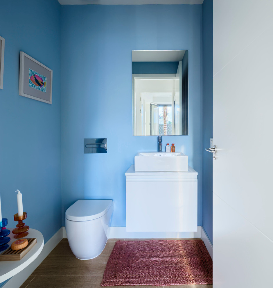 Inspiration for a small contemporary ceramic tile powder room remodel in Malaga with flat-panel cabinets, white cabinets, a one-piece toilet, blue walls and a vessel sink