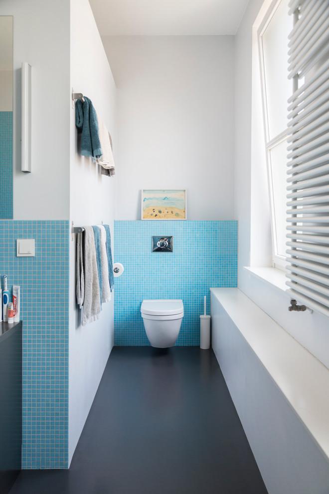 Foto de cuarto de baño contemporáneo con sanitario de pared, baldosas y/o azulejos azules, baldosas y/o azulejos en mosaico y paredes blancas
