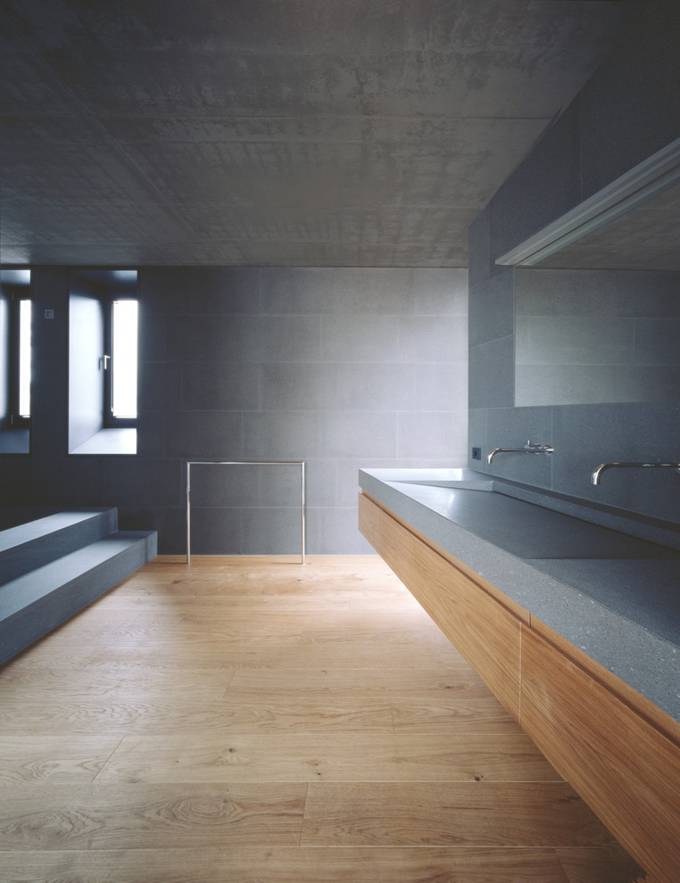 Bathroom - huge modern gray tile and cement tile light wood floor bathroom idea in Other with flat-panel cabinets, medium tone wood cabinets, an integrated sink and terrazzo countertops