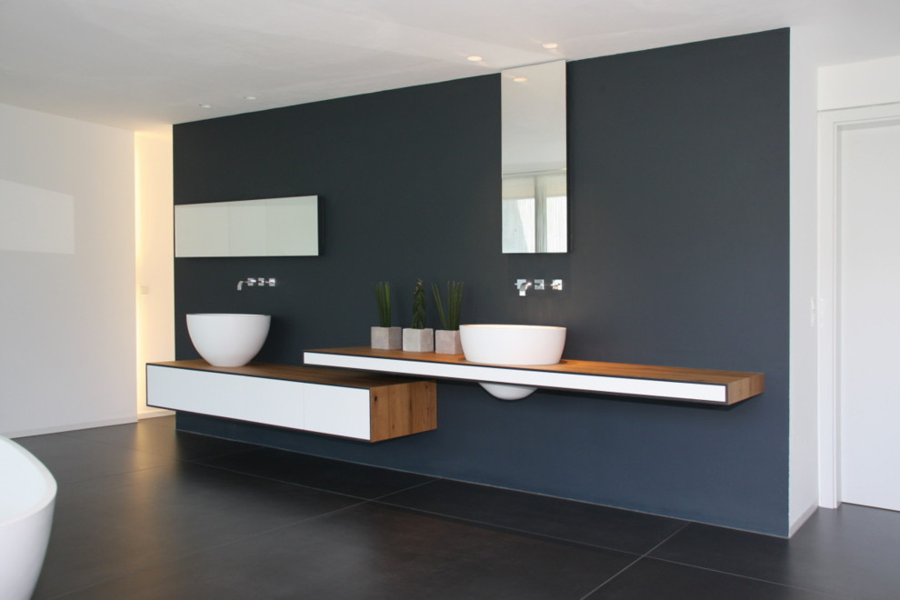 Large modern bathroom in Cologne with wooden worktops, a freestanding bath, grey walls, flat-panel cabinets, white cabinets, slate flooring and a vessel sink.