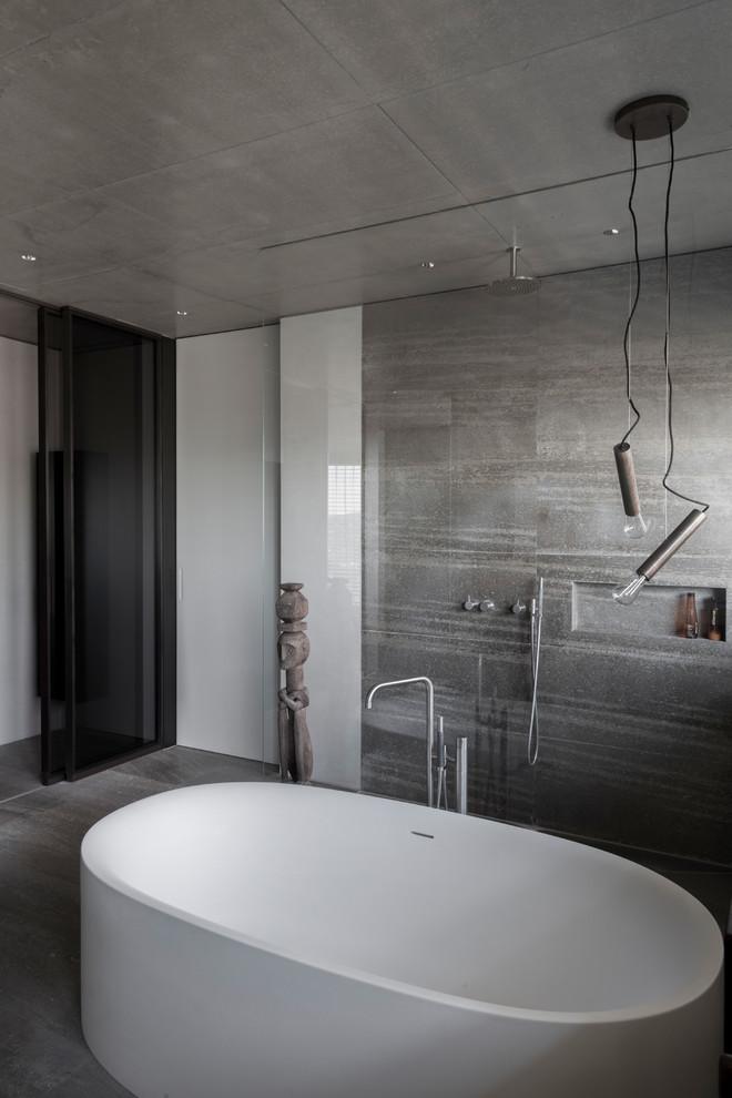 Immagine di una stanza da bagno con doccia industriale di medie dimensioni con vasca freestanding, doccia aperta, piastrelle beige, piastrelle grigie, pavimento in cemento, pavimento grigio e doccia aperta