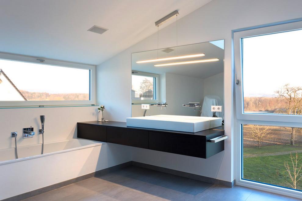 Imagen de cuarto de baño moderno, grande, con lavabo sobreencimera, armarios con paneles lisos, puertas de armario negras, bañera encastrada y paredes blancas