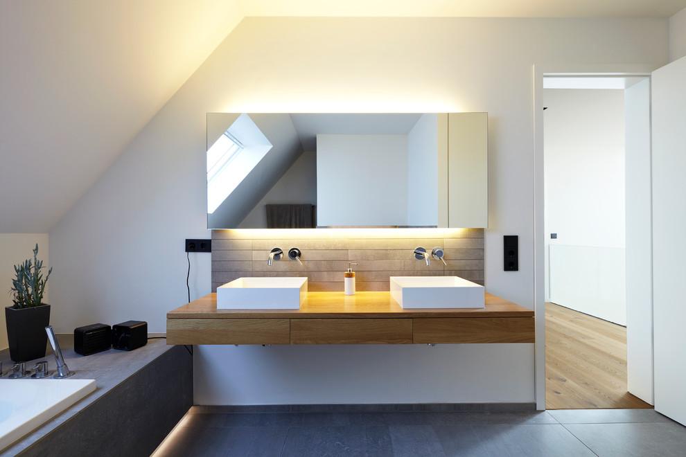 Diseño de cuarto de baño escandinavo, de tamaño medio, con lavabo sobreencimera, armarios con paneles lisos, puertas de armario de madera oscura, encimera de madera, bañera encastrada, baldosas y/o azulejos grises, baldosas y/o azulejos de piedra, paredes blancas y espejo con luz