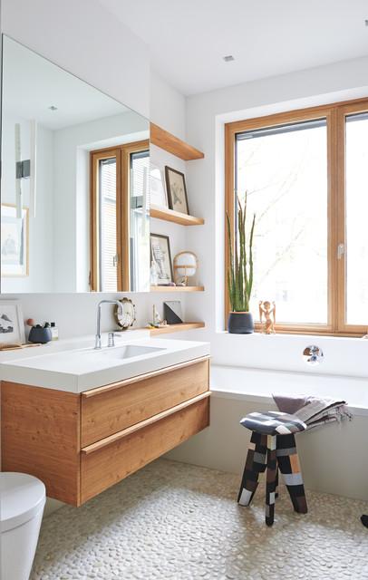 Idee per una piccola stanza da bagno nordica con vasca ad alcova, pareti bianche, pavimento con piastrelle di ciottoli, ante lisce, ante in legno scuro e lavabo integrato