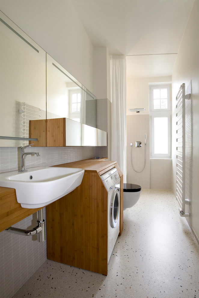 Example of a mid-sized trendy 3/4 gray tile and matchstick tile bathroom design in Berlin with flat-panel cabinets, medium tone wood cabinets, wood countertops, white walls and a drop-in sink