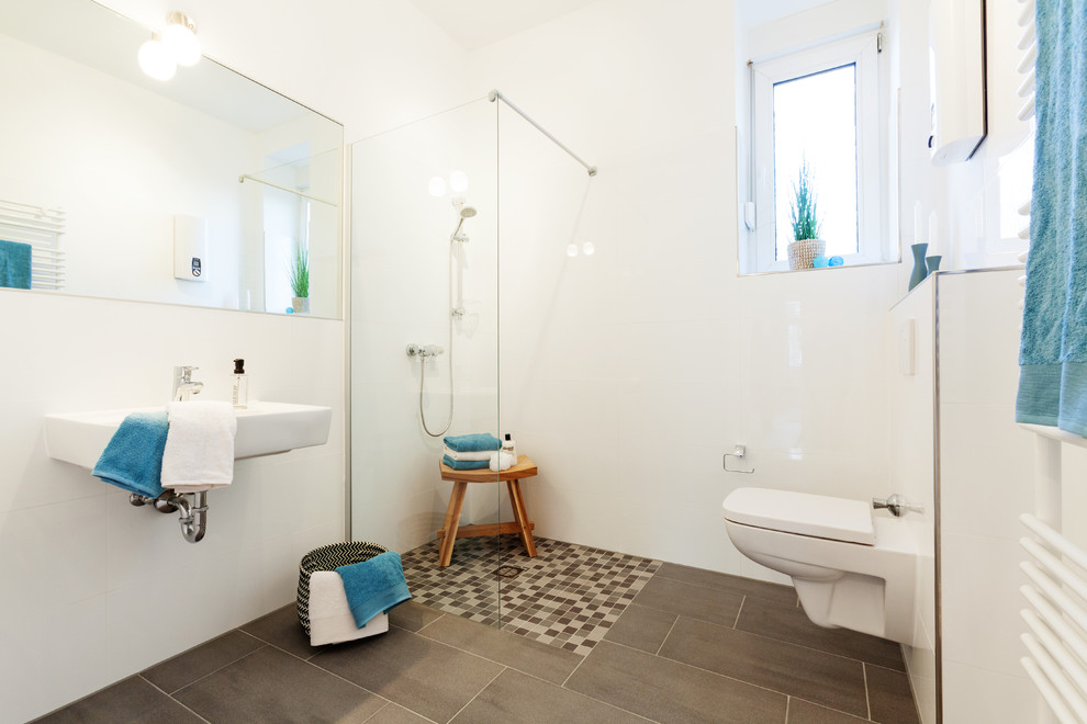 Corner shower - small scandinavian 3/4 gray tile and white tile corner shower idea in Essen with a wall-mount toilet, white walls and a wall-mount sink