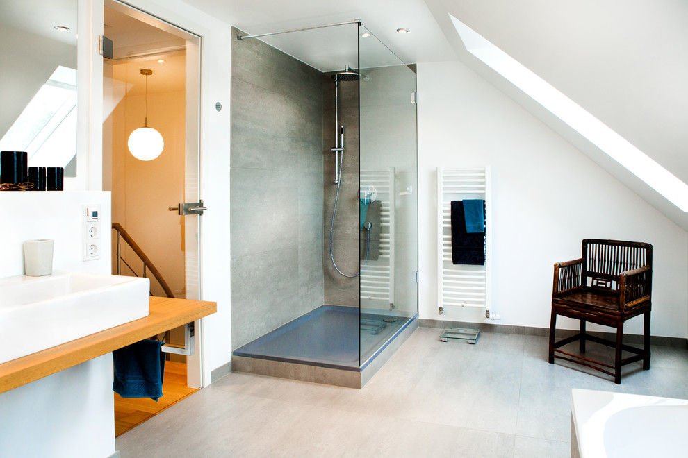 Inspiration for a large contemporary gray tile and stone slab gray floor bathroom remodel in Munich with white walls, a vessel sink, wood countertops and a wall-mount toilet