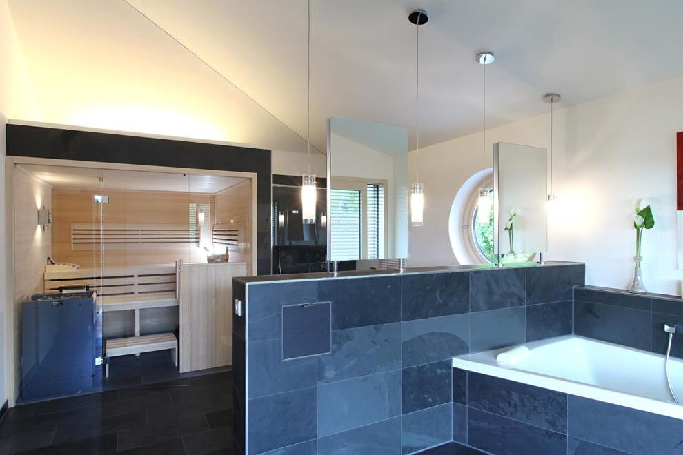 Modelo de sauna contemporánea, extra grande, con bañera empotrada, baldosas y/o azulejos negros, baldosas y/o azulejos de piedra, paredes blancas y suelo de pizarra