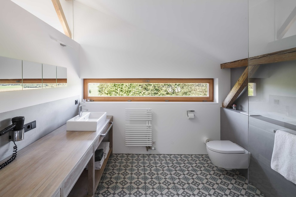 Bathroom - country gray tile cement tile floor and multicolored floor bathroom idea in Munich with open cabinets, medium tone wood cabinets, a wall-mount toilet, white walls, a vessel sink, wood countertops and brown countertops