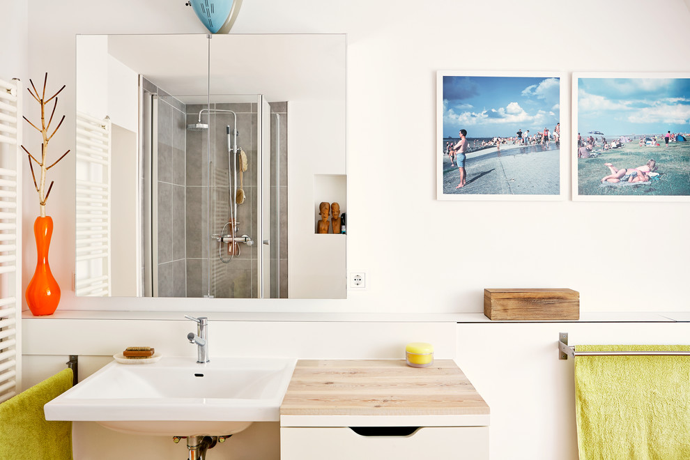Example of a mid-sized trendy corner shower design in Hamburg with flat-panel cabinets, beige cabinets, white walls, a wall-mount sink and wood countertops